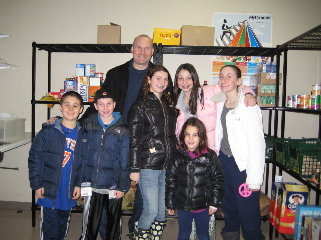 Danielle and the rest of the Klausner family in front of the results of her bat mitzvah project.