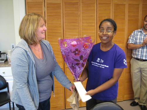 Doreen, our Administrative Coordinator, presents Roxie with a bouquet of flowers.