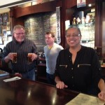 Robert (L) and Marsha (R) volunteer as guest bartenders while manager Paul looks on.
