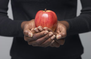 A woman holding a healthy apple